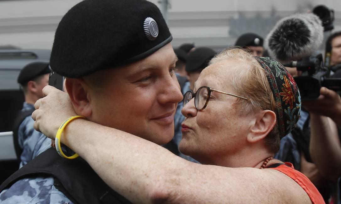 Manifestante beija um policial durante marcha a favor de Golunov Foto: MAXIM SHEMETOV / REUTERS