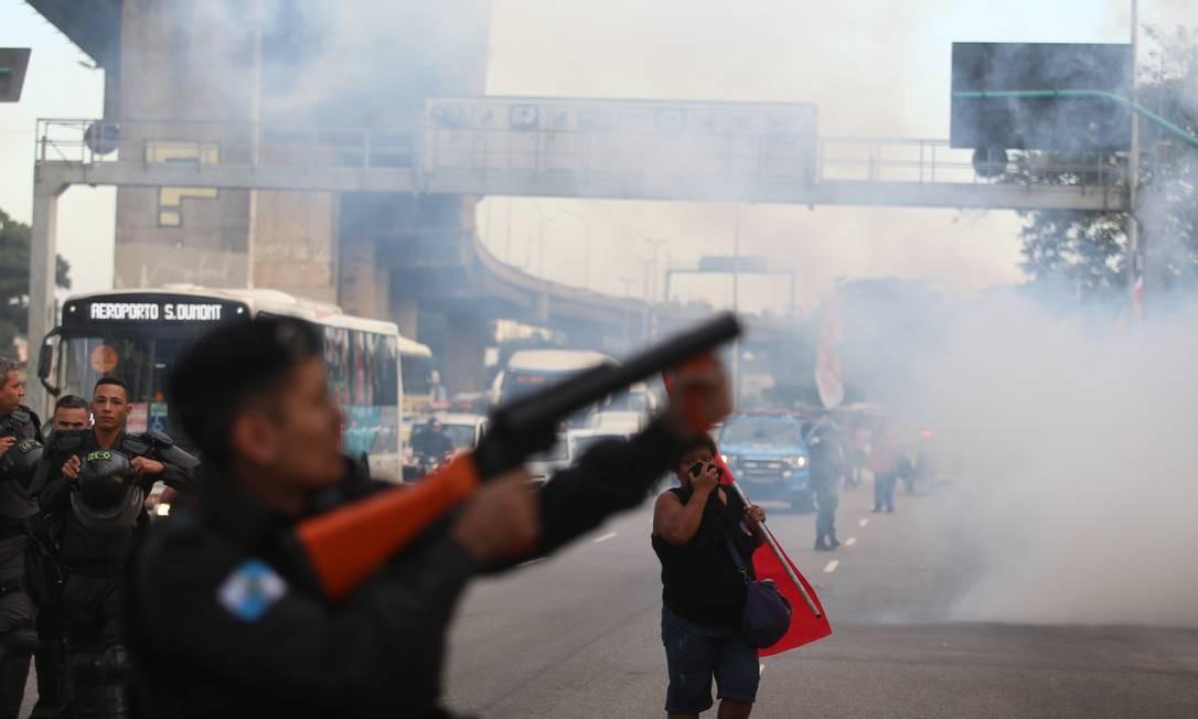 Policial lança bomba de efeito moral para dispersar manifestantes em frente ao Into Foto: Fabiano Rocha / Agência O Globo