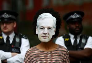 Manifestante contrária à extradição usa máscara de Assange na porta do tribunal Foto: HANNAH MCKAY / REUTERS