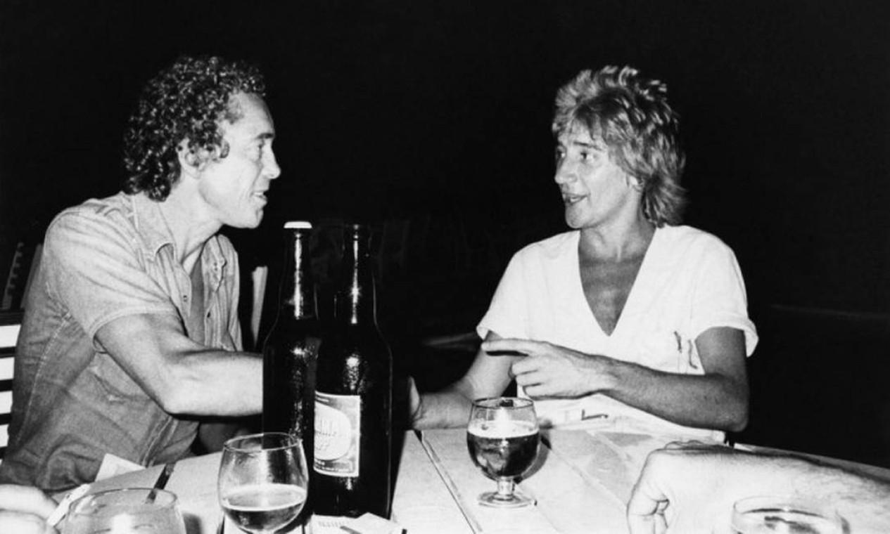 O produtor entre um copo e outro de cerveja com Rod Stewart, durante a passagem do britânico pelo Rio em 1977 Foto: Divulgação / Infoglobo