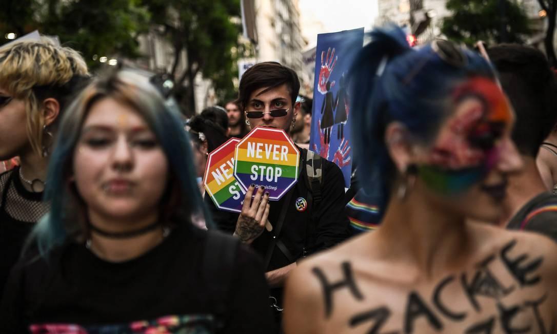 Homem segura placa onde se lê 'Never Stop (nunca pare) durante a parada do orgulho gay em Atenas, no dia 8 de junho de 2019 Foto: ARIS MESSINIS / AFP