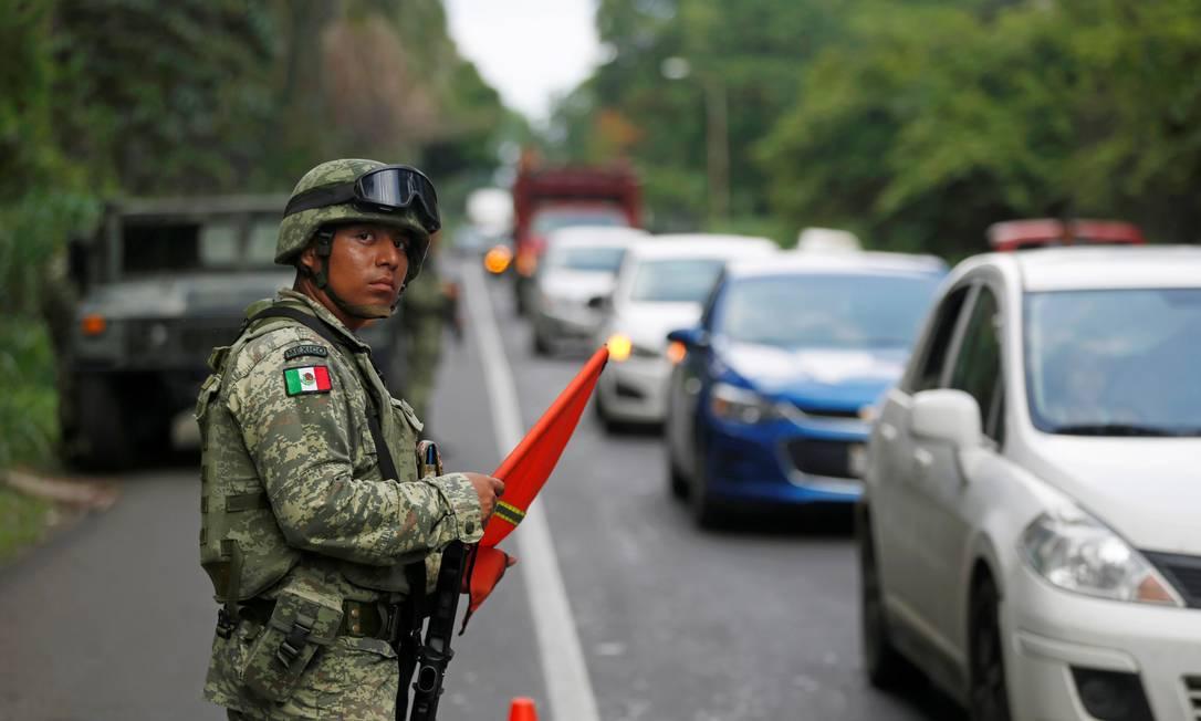 Um policial militar observa trânsito em um posto de controle ao longo em Tapachula, México Foto: JOSE CABEZAS / REUTERS