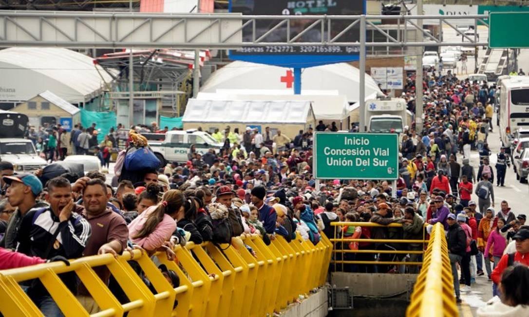 Venezuelanos aguardam na fronteira entre a Colômbia e o Equador, antes de seguirem rumo ao Peru Foto: DANIEL TAPIA / REUTERS