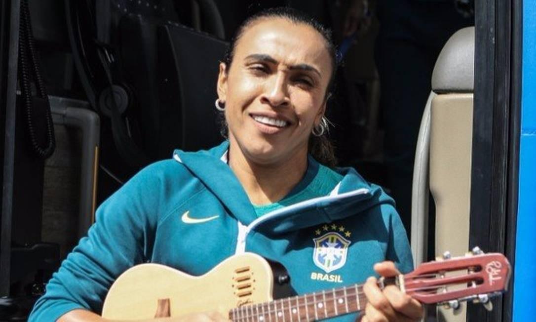 Marta toca cavaquinho na saída do ônibus da seleção Foto: Divulgação/CBF