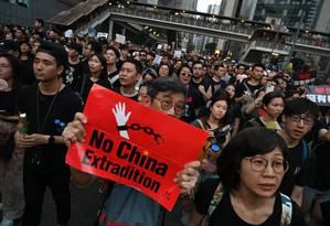 Manifestante segura cartaz contra a polêmica lei de extradição no protesto deste domingo: população da ex-colônia britânica teme ficar à mercê do nebuloso sistema Judiciário da China Foto: HECTOR RETAMAL/AFP