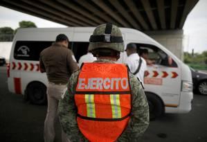 Soldado mexicano observa agentes de imigração durante uma abordagem em uma estrada de Tapachula, no dia 12 de junho. Foto: Jose Cabezas / REUTERS
