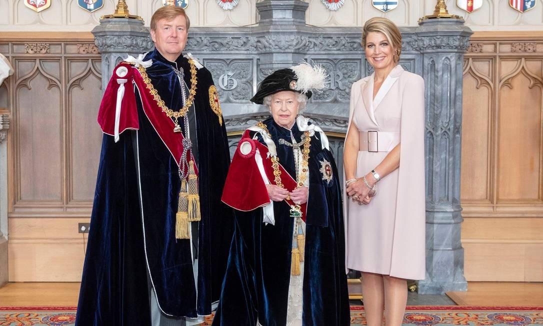Elizabeth II com o rei Guilherme, da Holanda, que também recebeu a Ordem da Jarreteira, a mais alta condecoração da cavalaria britânica. Ao lado, a rainha Máxima Foto: STEVE PARSONS / AFP