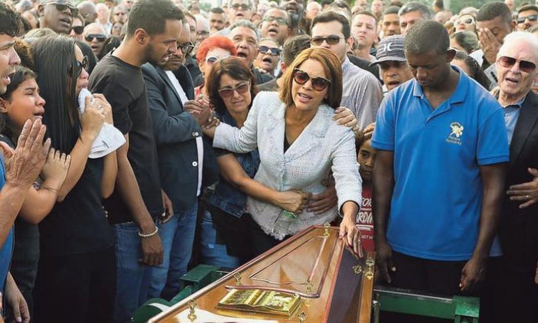 Flordelis põe a mão sobre o caixão durante o sepultamento, em São Gonçalo: durante a cerimônia, a deputada voltou a afirmar que Anderson foi morto em uma tentativa de assalto, hipótese praticamente descartada pela polícia Foto: Fabiano Rocha / Agência O GLOBO