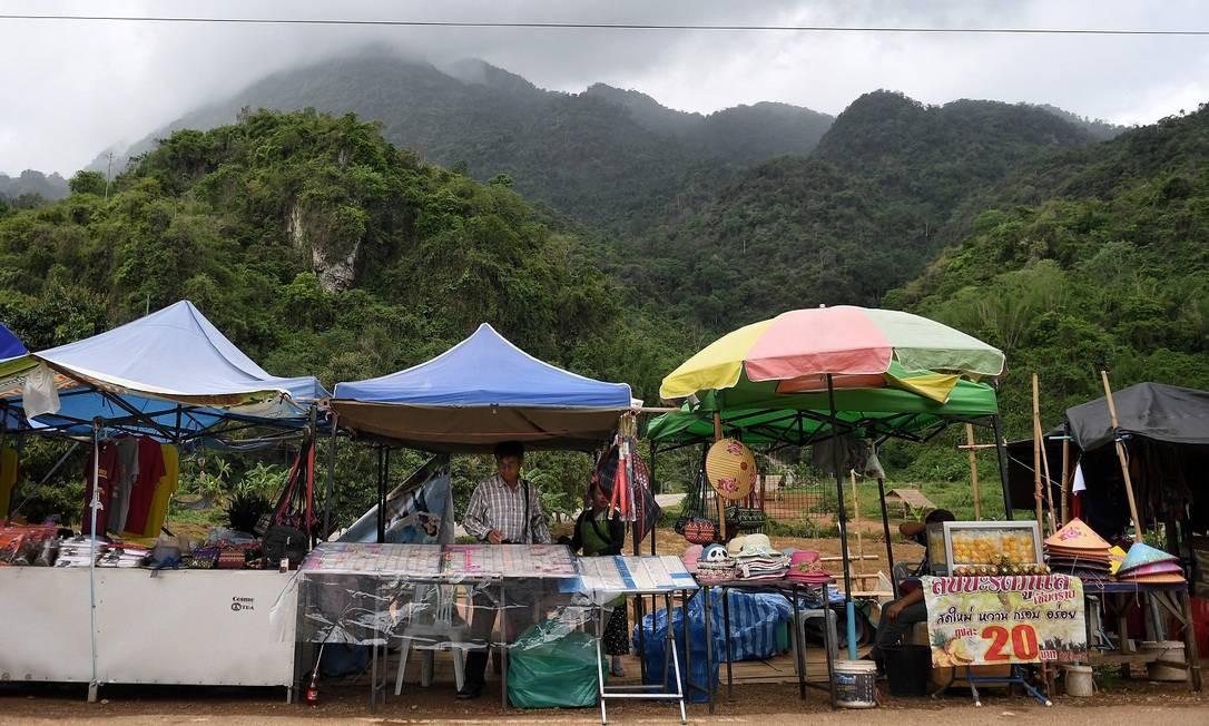 """Vendedores em barracas ao longo da estrada que leva à caverna de Tham Luang, na qual 12 garotos do time de futebol """"Javalis selvages"""" e seu técnico ficaram presos no ano passado, no distrito Mae Sai da província de Chiang Rai, na Tailândia Foto: LILLIAN SUWANRUMPHA / AFP"""