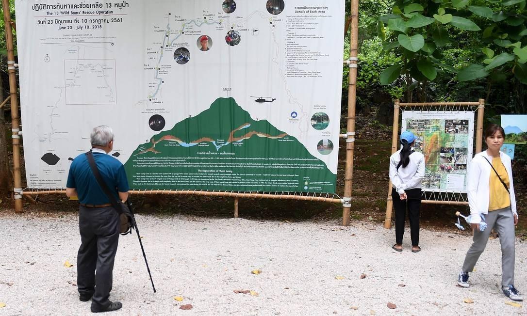 """Visitantes observam um infográfico ilustrando o resgate do time de futebol """"Javalis Selvagens"""" na caverna de Tham Luang Foto: LILLIAN SUWANRUMPHA / AFP"""