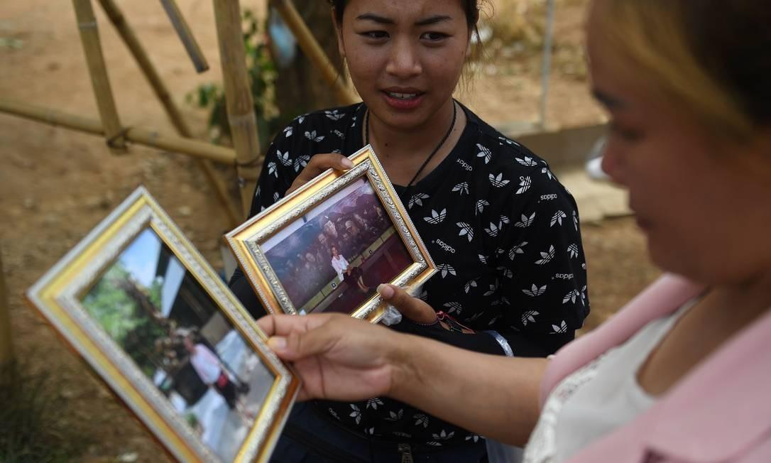 Vendedores com souvenirs perto da entrada da caverna de Tham Luang Foto: LILLIAN SUWANRUMPHA / AFP
