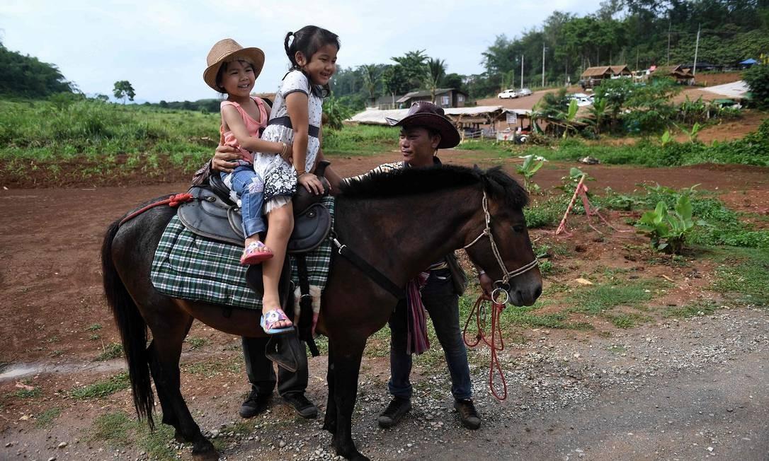 Meninas montando um pônei na estrada que leva à caverna de Tham Luang Foto: LILLIAN SUWANRUMPHA / AFP