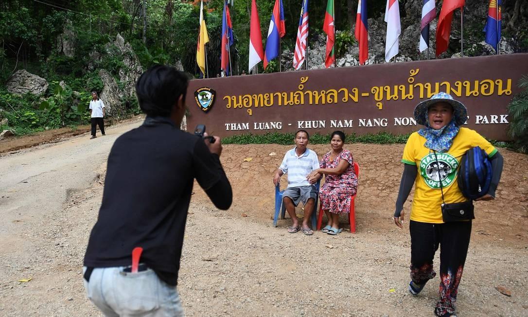 Turistas posam para fotos perto da entrada da caverna de Tham Luang Foto: LILLIAN SUWANRUMPHA / AFP