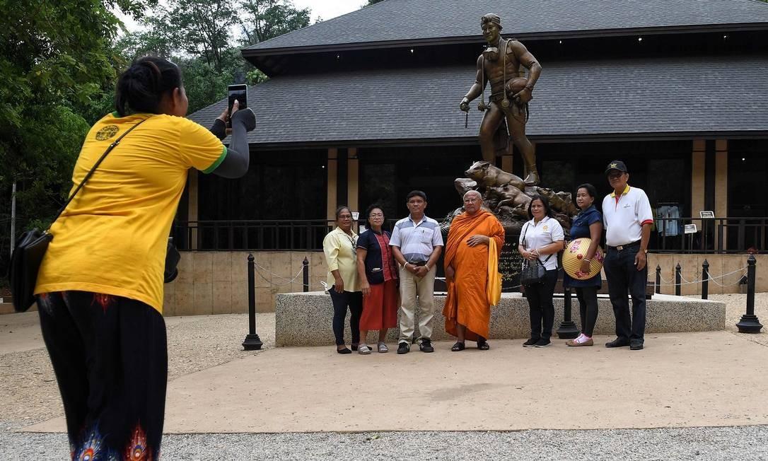 Visitantes posam para fotos na frente da estátua de Saman Gunan, o mergulhador tailandês que morreu durante os esforços para resgatar os 12 meninos e seu treinador que ficaram presos na caverna de Tham Luang no ano passado, no norte da Tailândia Foto: LILLIAN SUWANRUMPHA / AFP