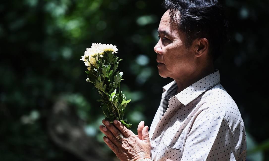 Visitante reza em frente à caverna de Tham Luang Foto: LILLIAN SUWANRUMPHA / AFP