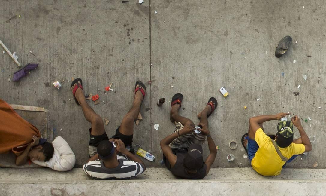 Na 'cracolândia' da Avenida Brasil, três jovens fumam crack, em meio à sujeira, e acampam à beira da via Foto: Márcia Foletto / Agência O Globo