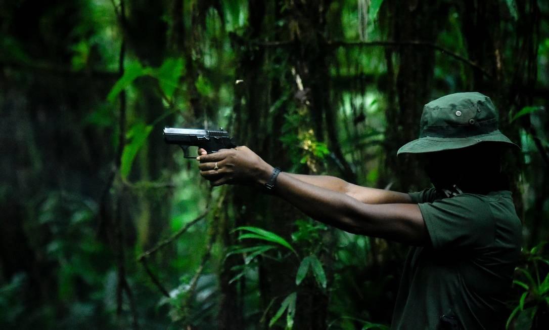 Integrante do Exército de Libertação Nacional pratica disparos com um revólver em uma região de mata fechada no departamento de Chocó, na Colômbia Foto: RAUL ARBOLEDA / AFP