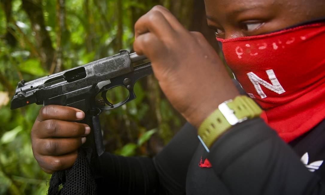 Guerrilheiro do Exército de Libertação Nacional limpa sua arma em acampamento do grupo no departamento de Chocó, na Colômbia Foto: RAUL ARBOLEDA / AFP