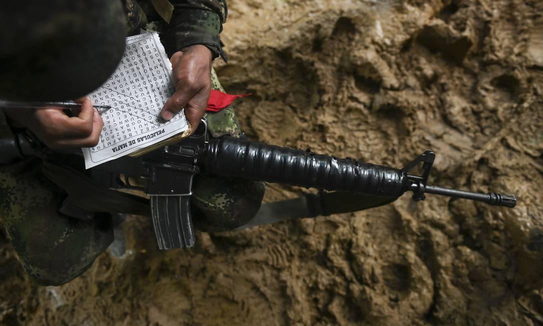Guerrilheiro faz palavras cruzadas depois de mais um deslocamento na selva colombiana. O Exército de Libertação Nacional é um dos grupos armados mais antigos das Américas, em operação desde a década de 1960 Foto: RAUL ARBOLEDA / AFP