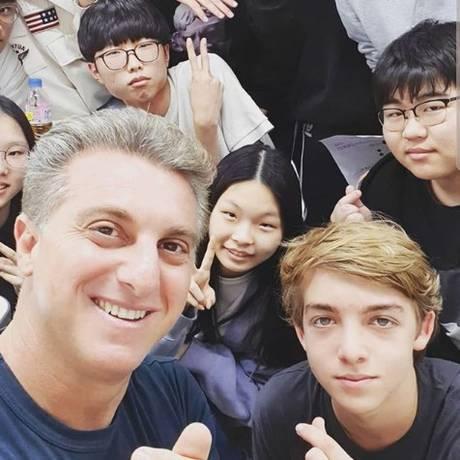Huck posa com o filho e estudantes da Coreia do Sul Foto: Reprodução