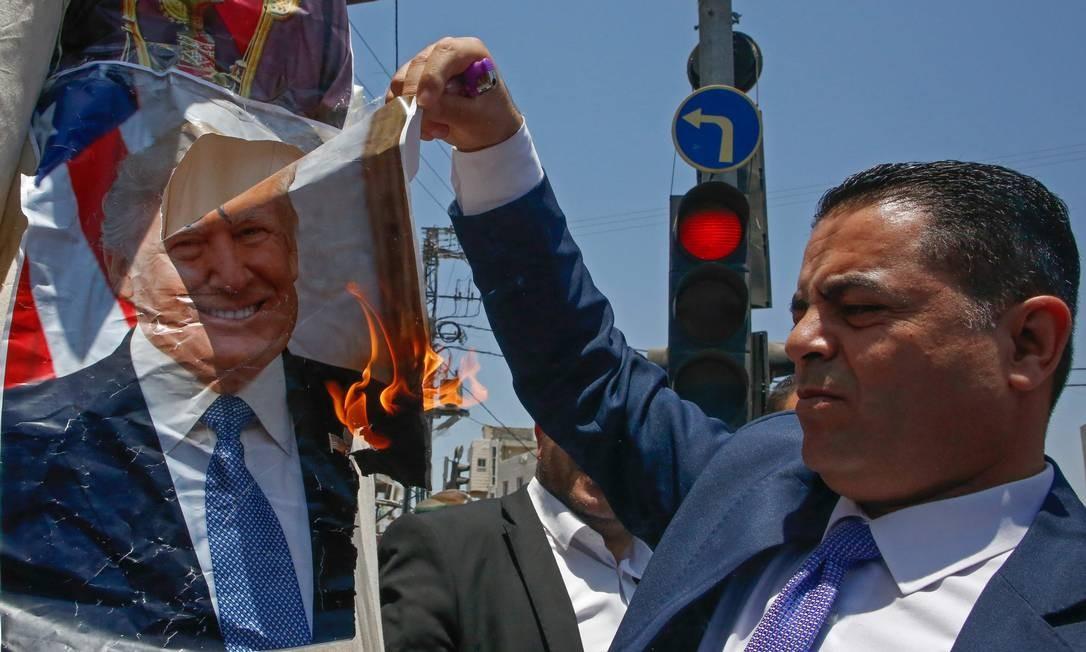 Homem palestino queima foto do presidente Donald Trump durante protestos contra plano econômico dos EUA para conflito árabe-israelense Foto: HAZEM BADER / AFP