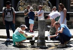Turistas bebem água e recarregam garrafas em uma fonte pública para se refrescar durante a onda de calor, em Roma; autoridades emitiram advertências contra desidratação e insolação, em particular para crianças e idosos, e hospitais foram colocados em alerta máximo Foto: ALBERTO PIZZOLI / AFP
