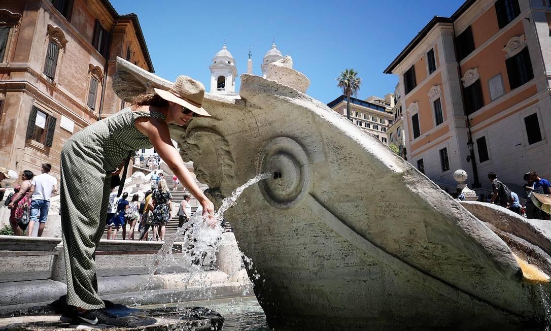 Uma mulher refresca-se na Fontana della Barcaccia, na Piazza di Spagna, no centro de Roma, durante uma onda de calor incomum no dia 24 de junho de 2019. Autoridades emitiram advertências contra desidratação e insolação, em particular para crianças e idosos, e hospitais foram colocados em alerta máximo Foto: ALBERTO PIZZOLI / AFP
