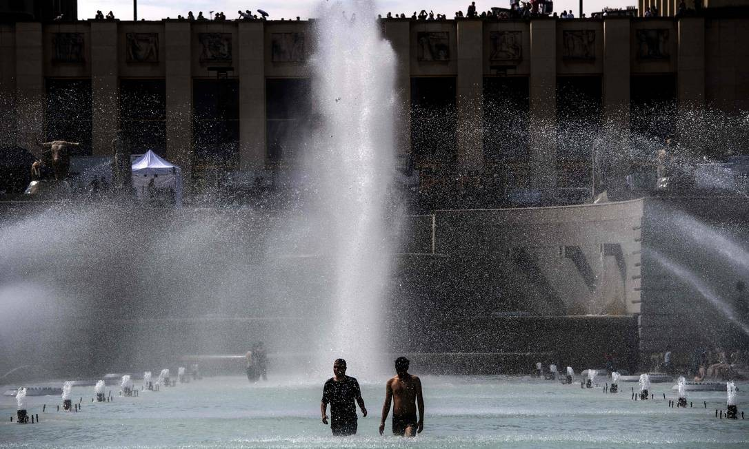 """People cool themselves down in a pond at the Trocadero esplanade in Paris on June 24, 2019, as temperatures soar to 33 degrees Celsius. - Forecasters say Europeans will feel sizzling heat this week with temperatures soaring as high as 40 degrees Celsius (104 degrees Fahrenheit) in an """"unprecedented"""" June heatwave hitting much of Western Europe. (Photo by Christophe ARCHAMBAULT / AFP) Foto: CHRISTOPHE ARCHAMBAULT / AFP"""