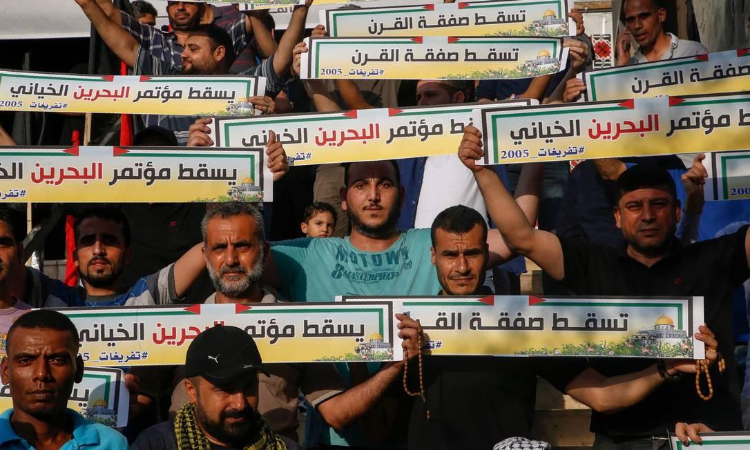 Palestinos seguram cartazes contra plano econômico dos EUA para conflito árabe-israelense na cidade de Gaza Foto: MOHAMMED ABED / AFP/25-06-2019