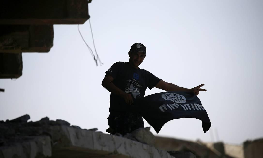 Integrante de forças de segurança do Iraque segura bandeira usada pelo grupo autointitulado Estado Islâmico. Desde a derrota dos extremistas na Síria e Iraque, autoridades de todo o mundo estão em alerta para possíveis ações de simpatizantes Foto: Thaier Al-Sudani / REUTERS