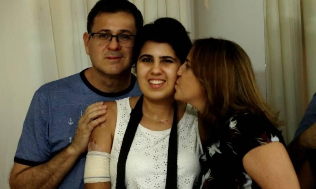 A jovem com o pai e a mãe, que estão dedicados em tempo integral à recuperação da filha Foto: Marcelo Theobald / Agência O Globo