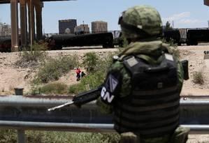 Integrante da Guarda Nacional do México observa imigrantes que atravessaram a fronteira rumo a El Paso, no Texas Foto: STRINGER / REUTERS