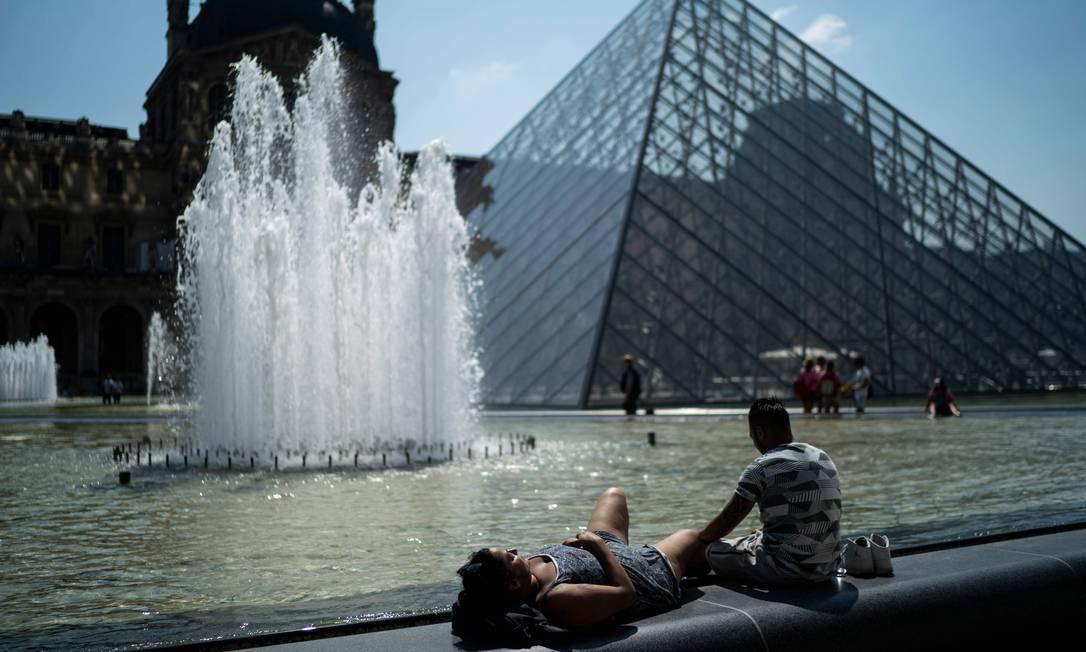 Pessoas tomam banho de sol em frente à pirâmide do Louvre durante onda de calor em Paris Foto: KENZO TRIBOUILLARD / AFP