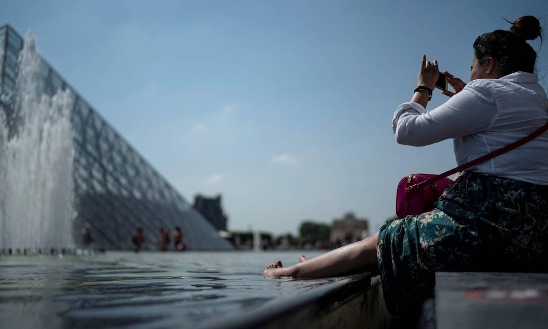 """Mulher mergulha os pés em fonte perto da pirâmide do Louvre, em Paris. Segundo meteorologistas, onda de calor """"sem precedentes"""" atinge grande parte da Europa Ocidental neste mês de junho Foto: KENZO TRIBOUILLARD / AFP"""