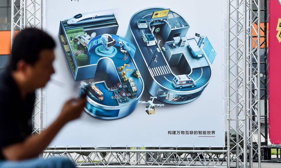Cartaz anuncia a tecnologia 5G durante feira na China. Huawei é uma das líderes no desenvolvimento da tecnologia, mas a empresa é acusada pelos EUA de agir a serviço do governo chinês. Ela está no centro de uma disputa entre os dois países Foto: HECTOR RETAMAL / AFP