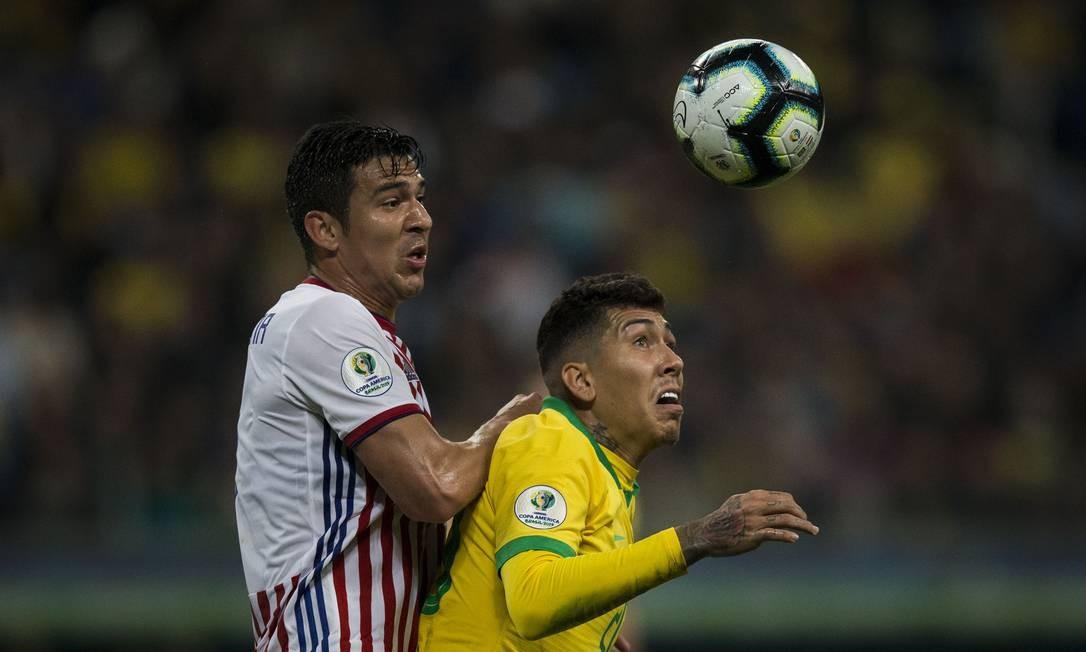Firmino recebe a marcação de um jogador do Paraguai Foto: Guito Moreto / Guito Moreto