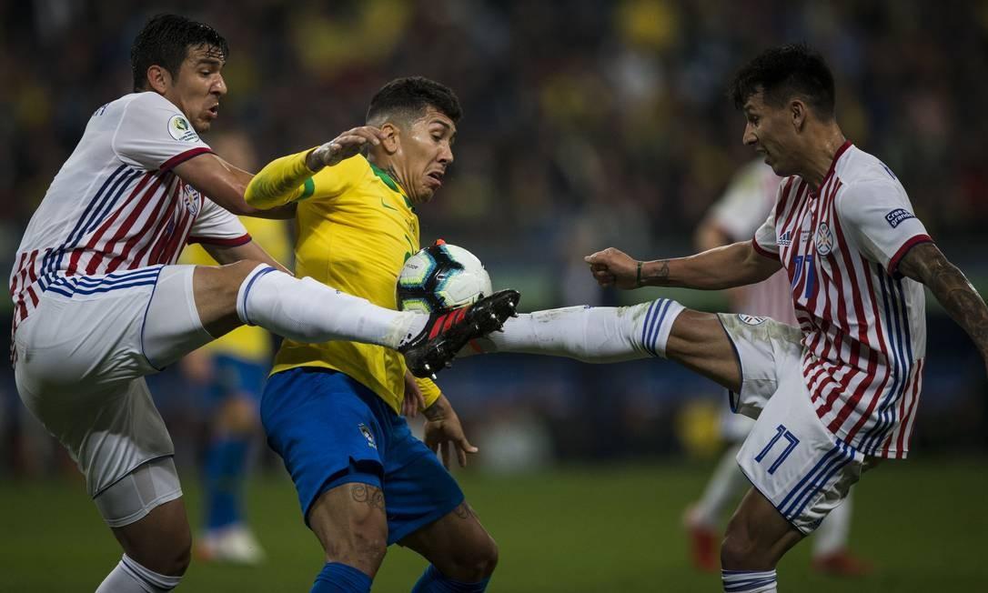 Firmino disputa a bola com dois marcadores do Paraguai Foto: Guito Moreto / Guito Moreto