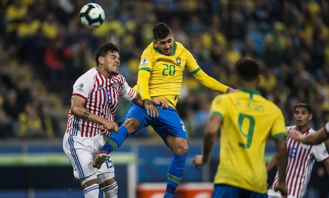 Firmino disputa no alto a bola com Gómez Foto: Guito Moreto / Guito Moreto