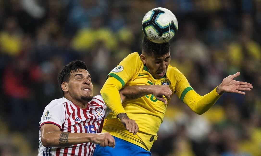 Firmino trava disputa aérea com jogador do Paraguai Foto: Guito Moreto / Guito Moreto