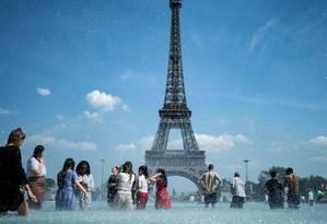 Pessoas se resfrescam na fonte da esplanada do Trocadero, em Paris. Foto: KENZO TRIBOUILLARD / AFP