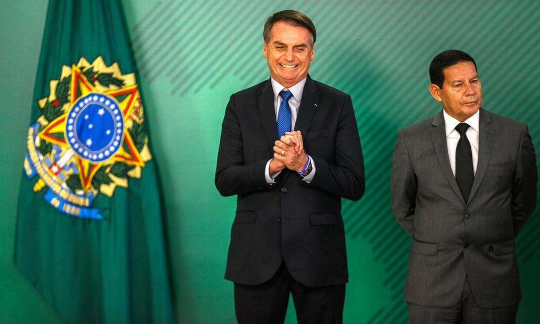 Bolsonaro durante cerimônia de assinatura da MP que visa coibir fraudes no INSS, ao lado do vice-presidente, general Hamilton Mourão Foto: Daniel Marenco / Agência O Globo