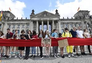 Jovens ativistas formam uma corrente humana em frente ao parlamento alemão para pressionar por medidas efetivas contra aquecimento global Foto: TOBIAS SCHWARZ / AFP
