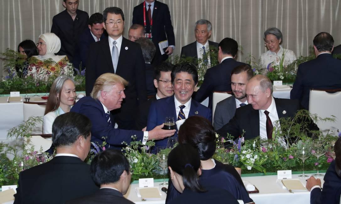 O presidente russo, Vladimir Putin, brinda com o americano Donald Trump utilizando um copo térmico Foto: HANDOUT / REUTERS