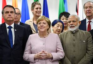 Bolsonaro ao lado de Angela Merkel na cúpula do G20 Foto: BRENDAN SMIALOWSKI / AFP