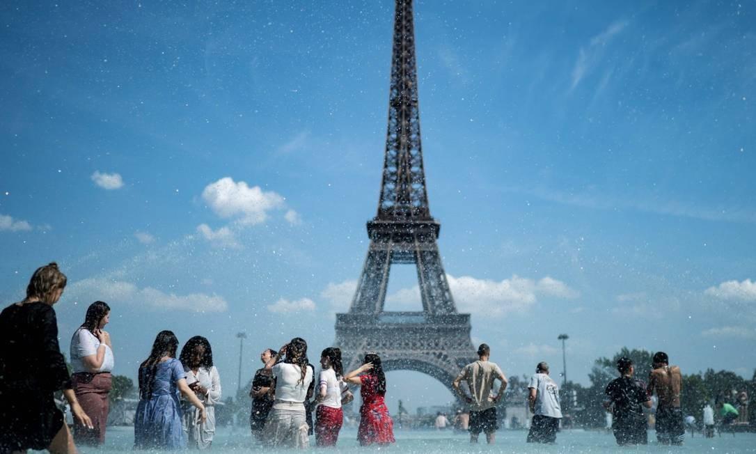 Pessoas se banham em frente à Torre Eiffel para aliviar o calor Foto: KENZO TRIBOUILLARD / AFP