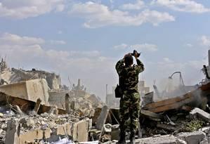 Soldado inspeciona os escombros de um centro de pesquisas em Damasco após bombardeio israelense ocorrido em 14 de abril. Ataques como o da noite deste domingo são cada vez mais frequentes na Síria. Israel diz que o Hezbollah e o Irã usam o território do país como base para lançar ataques contra o país. Foto: LOUAI BESHARA / AFP