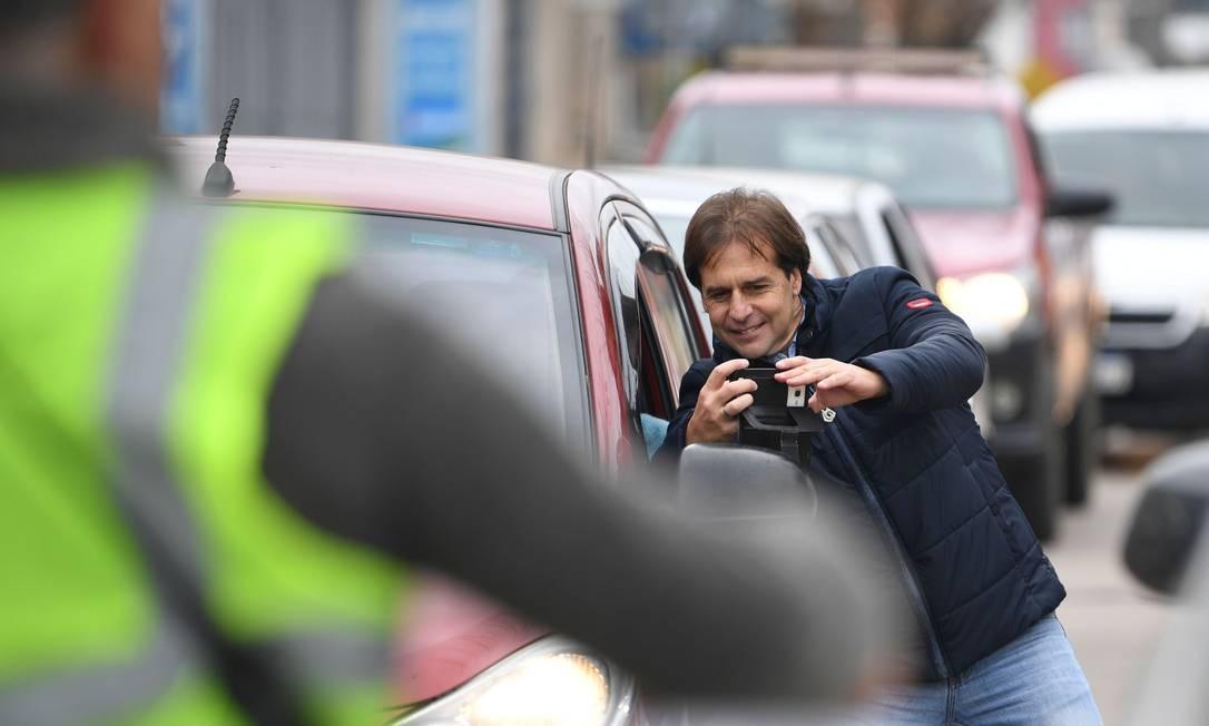 O pré-candidato pelo Partido Nacional Luis Lacalle Pou tira selfie com apoiador após votar nas primárias no Uruguai Foto: PABLO PORCIUNCULA / AFP