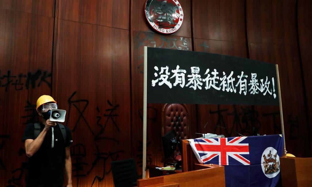 Manifestante coloca bandeira colonial britânica de Hong Kong na tribuna do plenário do Parlamento da cidade. Ao seu lado, uma faixa que diz