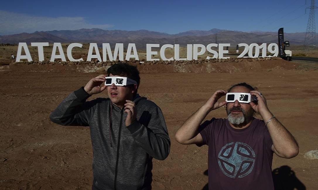 SOC - Turistas com óculos especial para assistir ao eclipse solar total em campo astronômico no deserto do Atacama Foto: MARTIN BERNETTI / AFP