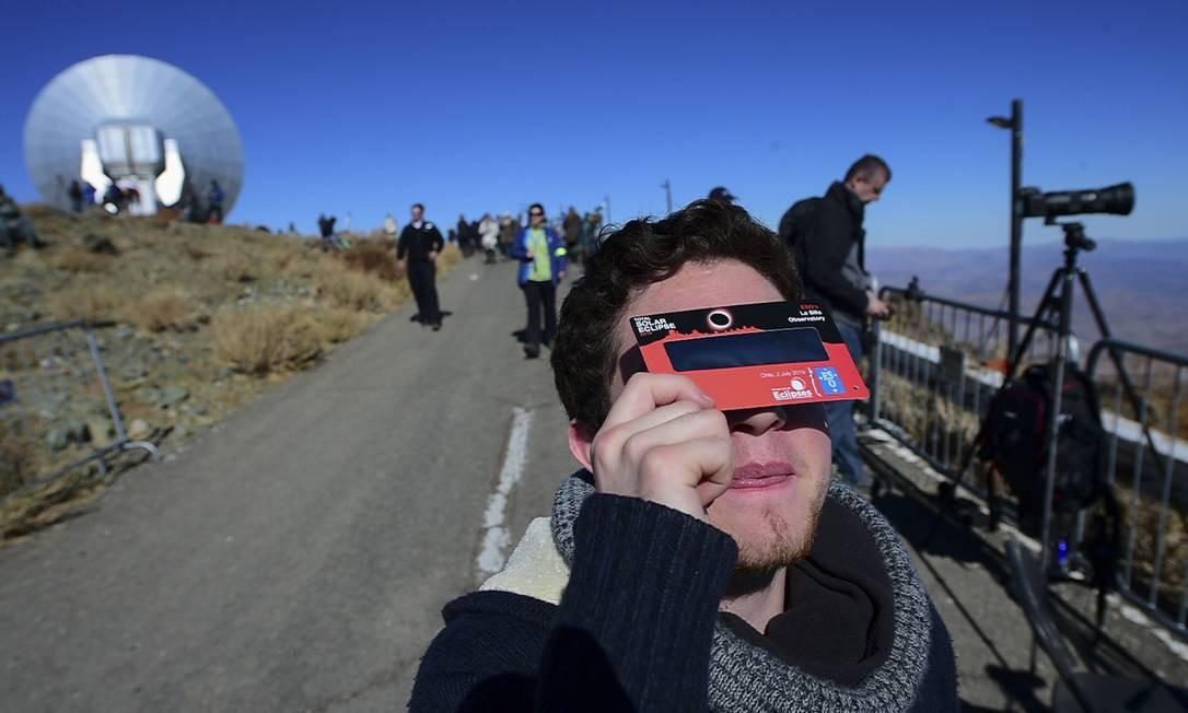 Turista experimenta óculos especiais no Observatório La Silla para observar o eclipse solar em La Higuera, Região de Coquimbo, Chile. O dia se tornará noite nesta terça em grande parte do Chile e da Argentina devido ao eclipse total do sol, mergulhando uma vasta faixa do Pacífico Sul e do cone da América do Sul na escuridão Foto: MARTIN BERNETTI / AFP